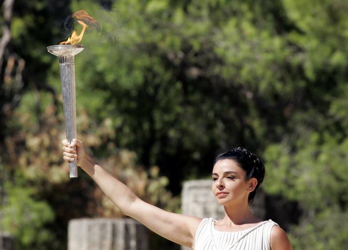 Театрализованное представление заключается в том, что 11 женщин в греческих костюмах сопровождают факел, который зажигает от солнца одна из них — жрица Протиериа. Затем она передаёт его первому спортсмену-факелоносцу. Фото: Milos Bicanski/Getty Images