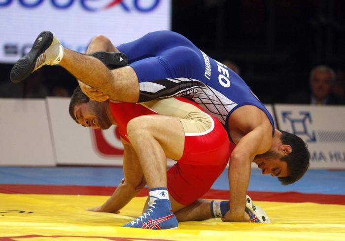 В категории до 66 килограммов третье место занял Магомед Курбаналиев (в красном)в борьбе с представителем Грузии Леваном Келехсашвили. Фото: FERENC ISZA/AFP/Getty Images