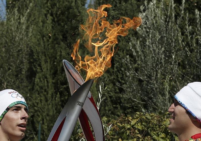 Греческий атлет Яннис Антониу передал эстафету олимпийского огня Игр «Сочи-2014» российскому хоккеисту Александру Овечкину, 29 сентября 2013 года. Фото: DIMITRI MESSINIS/AFP/Getty Images