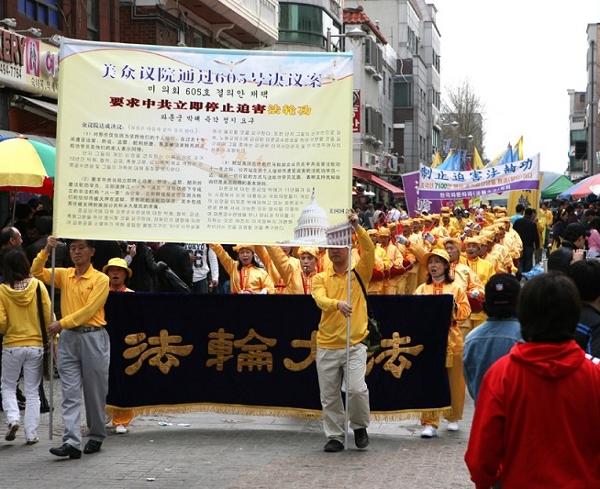 Плакат с вступлением к исторической хронике «Девять комментариев о коммунистической партии», позади колонна барабанщиков. Фото: Xi Tai/The Epoch Times