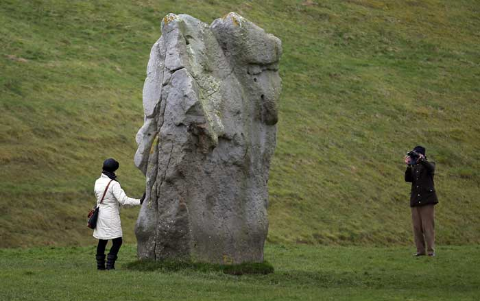 Туристы фотографируются рядом с древним английским памятником. Эйвбери-хендж – один из самых старейших и крупных мегалитических памятников Европы. Он расположен на территории английского графства Уилтшир и датируется 2600 годом до н.э. Фото: Matt Cardy/Getty Images