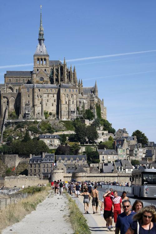 Туристы осматривают Мон-Сен-Мишель - небольшой скалистый остров-крепость, на северо-западном побережье Франции. Фото: CHARLY TRIBALLEAU/AFP/GettyImages