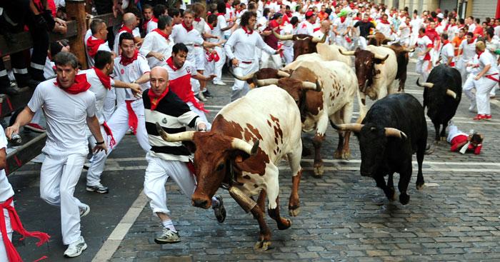 Люди убегают от быков на фестивале Сан-Фермин в Памплоне, Испания. Фото: RAFA   RIVAS/AFP/Getty Images