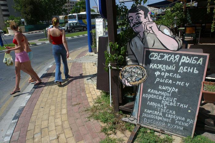 Туристы проходят мимо меню на русском языке, размещённого рядом с рестораном в Лимассоле. фото: LAURA BOUSHNAK/AFP/GettyImages