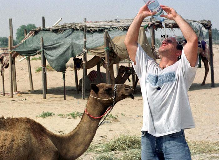Турист льет воду себе на голову, чтобы охладиться, Дубай, ОАЭ. Фото: EDDY PADO/AFP/Getty Images