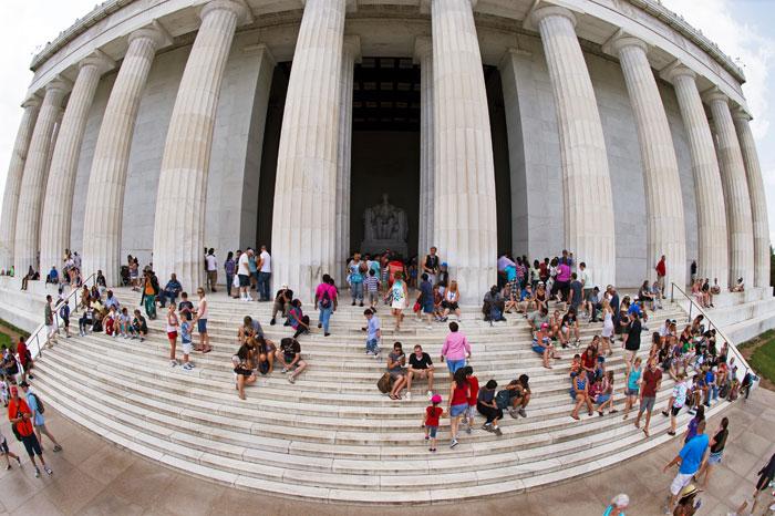 Туристы сидят на ступенях Мемориала Линкольна, Вашингтон, округ Колумбия, США. Фото:  PAUL J. RICHARDS/AFP/GettyImages