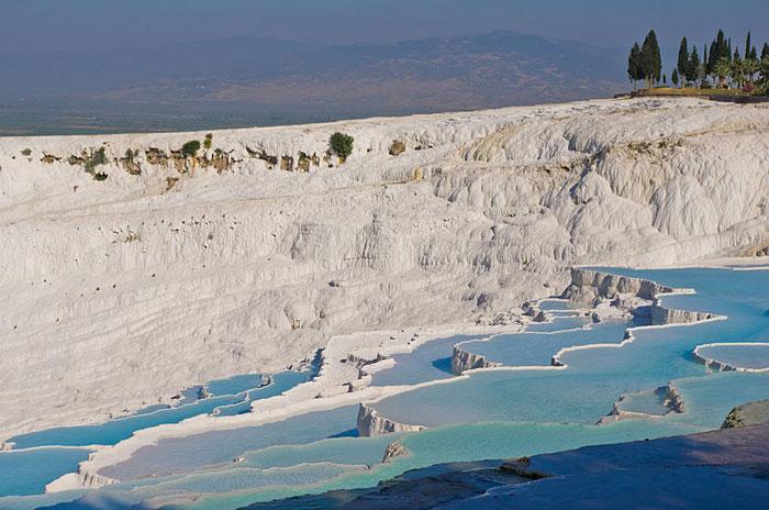 Памуккале - природный объект в провинции Денизли на юго-западе Турции. В него входят 17 геотермальных источников с температурой воды от 35 до 100 °C и водоемы-террасы, образовавшиеся из травертина. Фото: Antoine Taveneaux/commons.wikimedia.org