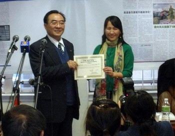 Чжан Кайчэнь (слева), директор отделения по связям отдела пропаганды комитета компартии Китая в Шеньяне, принимает свидетельство, подтверждающее его выход из КПК
