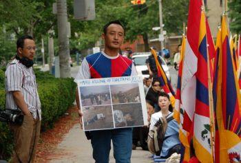 Житель Тибета  выступает с акцией протеста перед китайским консульством в Торонто. У него в руках фотографии жителей Тибета, погибших от разрывных пуль.  Фото: Мэтью Литл/ Великая Эпоха