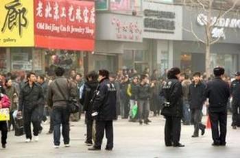 Полиция патрулирует торговую улицу Ваньфуцзин в Пекине, на которой 20 февраля 2011 года собрались манифестанты. Распространенные по Интернету сообщения призвали недовольных китайцев собраться в 13 крупных городах Китая в людных местах по образцу «Жасминовой революции», охватившей Ближний Восток. Фото: Peter Parks /AFP /Getty Images