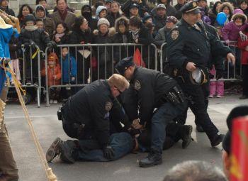 Хулиганство: полиция арестовывает человека, который прорвался сквозь ограждение и порвал плакат последователей Фалуньгун во время новогоднего парада во Флашинге 12 февраля. Фото: Джошуа Филипп /Великая Эпоха