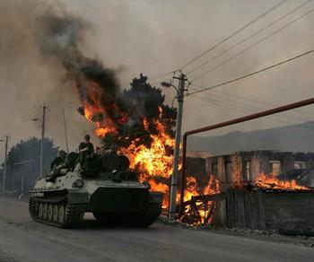 Русские солдаты проезжают мимо разрушенного южноосетинскими войсками дома в грузинской деревне Кьемо-ашебети, что в 5 км от Цхинвали, 18 августа 2008 г. Фото: DMITRY KOSTYUKOV/AFP/Getty Images