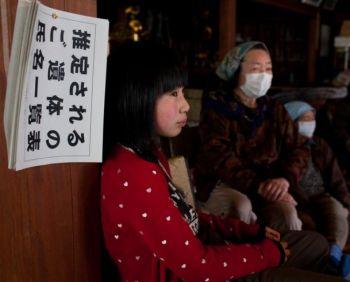На стене висит список жертв, пострадавших при землетрясении и цунами. Японские беженцы  в буддистском храме, используемом в качестве центра эвакуации, в Офунато, префектура Иватэ, 4 апреля 2011 года. Фото: Yasuyoshi Chiba / Getty Images
