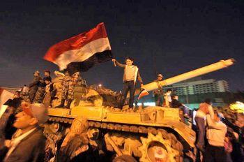 Египетская девушка размахивает национальным флагом на танке М-60, во время празднования антиправительственных демонстраторов в Каире на площади Тахрир, после того как президент Египта Хосни Мубарак ушел в отставку. Фото: Patrick Baz/AFP/Getty Images