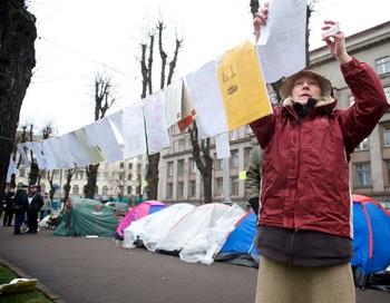 11 человек живут в палатках напротив здания правительства Латвии, протестуя против отнятой пенсии. Женщина вывешивает на скрепках ошибки правительства. 11 декабря. Рига, Латвия. Фото:  ILMARS ZNOTINS/AFP/Getty Images