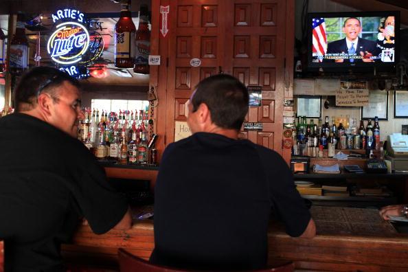 Люди в пораженном нефтью участке Мексиканского залива слушают в баре речь Барака Обамы, как он обсуждают нефтяное пятно. Фото: Platt/Getty Images