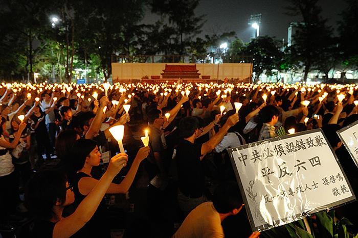Участники акции, посвящённой 23-й годовщине бойни на площади Тяньаньмэнь, держат плакаты и зажжённые свечи. На баннерах написано: «Коммунистическая партия Китая должна извиниться перед жертвами бойни на Тяньаньмэнь и реабилитировать их». Фото: Sung Pi Lung/The Epoch Times