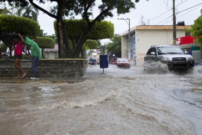 Тропический шторм Isaac  24 августа 2012 года принёс проливные дожди  в Enriquillo, расположенного на юго-западе Доминиканской Республики. Фоторепортаж. Фото:  ERIKA SANTELICES/AFP/GettyImages)
