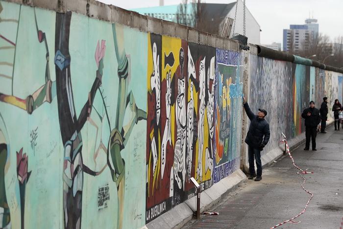 Берлинскую стену демонтируют с многочисленными граффити на ней. Фото: Sean Gallup/Getty Images