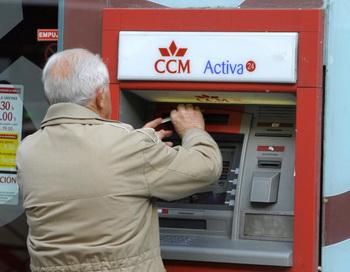 Испанец снимает деньги в банкомате. Фото: PHILIPPE DESMAZES/AFP/Getty Images