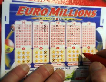 С надеждой на выигрыш участник лотереи заполняет лотерейный билет. Фото: FRANCOIS GUILLOT/AFP/Getty Images
