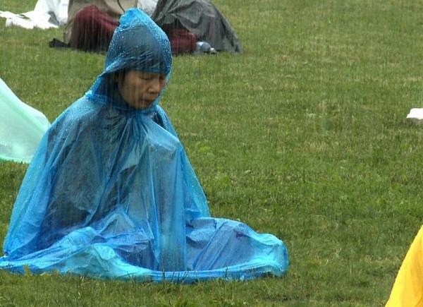Последователь Фалуньгун медитирует под проливным дождем возле Парламентского холма 24 июня во время визита Ху Цзиньтао в Канаду для участия в саммите G20. Фото предоставлено телекомпанией NTDTV