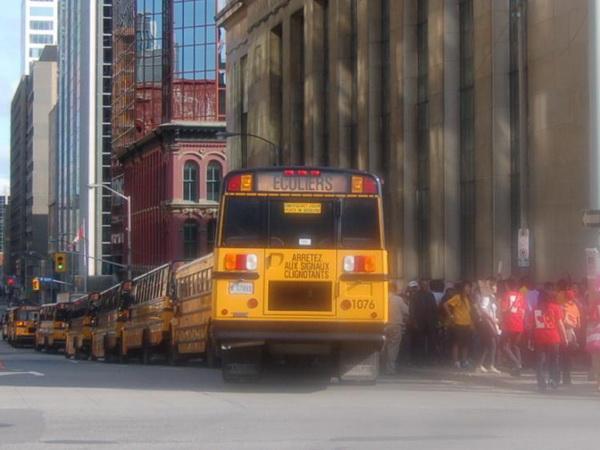 Большая колонна школьных автобусов в центре Оттавы, рядом со зданием канадского парламента, Парламентским холмом. Китайское посольство в Оттаве на этой неделе приложило большие усилия, чтобы собрать китайцев со всей страны для приветствия прибывающего в Канаду Ху Цзиньтао. Некоторым студентам, обучающимся в Канаде на китайскую государственную стипендию, было даже сказано, что участие в митинге в честь прибытия Ху Цзиньтао обязательно. Фото: Cindy Gu/Великая Эпоха/The Epoch Times