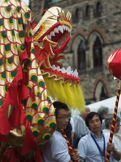 Китайцы, приветствующие Ху Цзиньтао, держат в руках куклы китайских драконов, которые используются в танцах. Фото: Matthew Little/Великая Эпоха/The Epoch Times