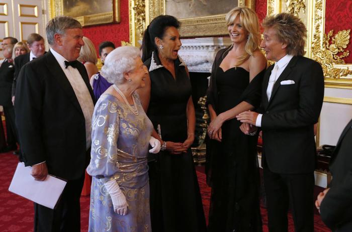 Королева Елизавета II приветствует Пенни Ланкастер (2, п) и Род Стюарт (п) на приёме во дворце Сент-Джеймс. Фото: Jonathan Brady - WPA Pool/Getty Images