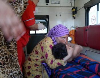 Женщина обнимает в машине скорой помощи потерпевшего мальчика, Сирия. Фото: -/AFP/GettyImages