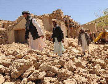 Афганские мужчины проходят мимо развалин домов после землетрясения. Фото: MASSOUD HOSSAINI/AFP/Getty Images