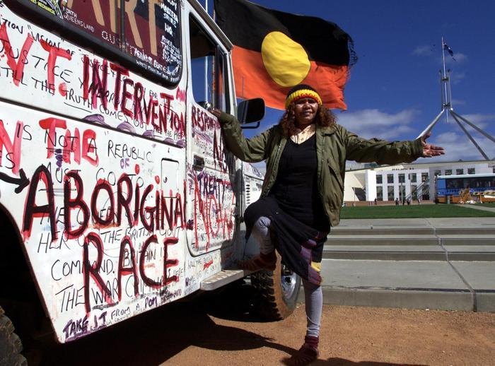 Коренная жительница Австралии с флагом аборигенов и протестом перед зданием правительства в 2000 году. Фото: BLACKWOOD/AFP/Getty Images