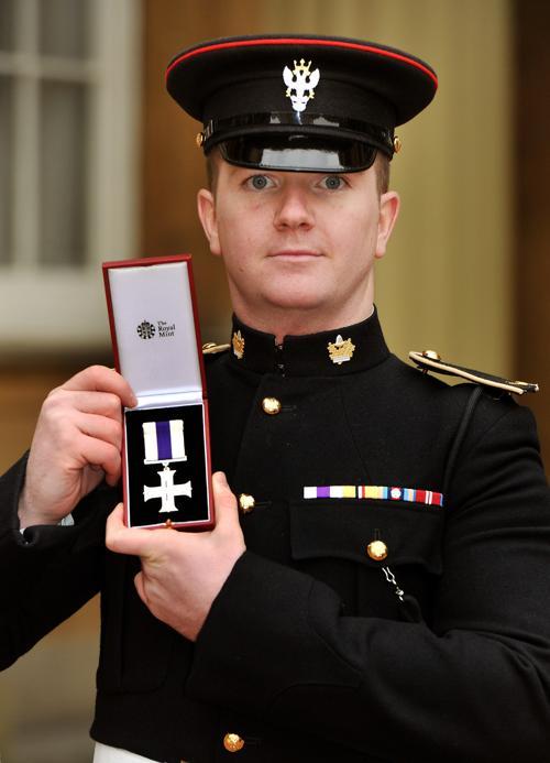 Капрал Карл Тейлор держит военный крест, врученный ему принцем Уэльским на церемонии инвеституры в Букингемском дворце, 25 января 2013 года. Фото: John Stillwell - WPA Pool/Getty Images