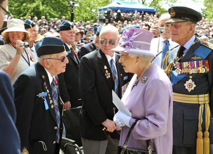 Королева Елизавета II и принц Филипп, герцог Эдинбургский. Королева говорит с ветераном Великой Отечественной войны Эдом Картером-Эдвардсом, бывшим членом бомбардировочной авиации из Канады, после открытия Мемориала бомбардировочной авиации в Лондоне, Англия. Фото: John Stillwell - WPA Pool/Getty Images