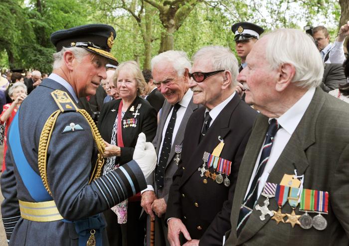 Принц Чарльз, принц Уэльский говорит с ветеранами Второй мировой войны, бывшими бомбардировщиками ВВС, после того, как королева Елизавета II представила Мемориал бомбардировочной авиации в Лондоне, Англия. Фото: John Stillwell - WPA Pool/Getty Images