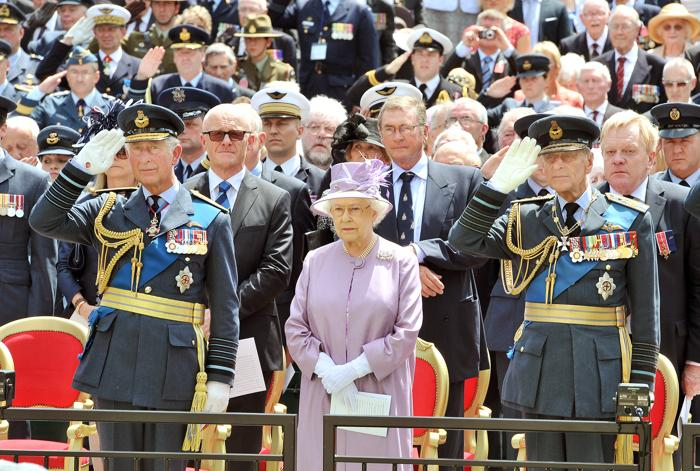 Принц Чарльз, принц Уэльский и принц Филипп, герцог Эдинбургский отдают честь рядом с  королевой Елизаветой II во время церемонии официального открытия Мемориала бомбардировочной авиации в Лондоне, Англия. Фото: John Stillwell - WPA Pool/Getty Images