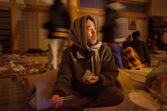 Мужчина ест консервированную рыбу в центре для пострадавших от землетрясения. Кесеннума, Япония, 23 марта 2011 год. Фото: Paula Bronstein/Getty Images