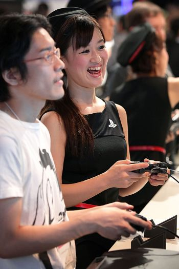 Популярное развлечение: ассистент с посетительницей играют в игру в сети PlayStation с пультом оператора на 3 видео-игры на демонстрации компьютеров Sony Inc. во время телевикторины Токио-2010 16 сентября 2010 г. в Чиба, Япония. Фото: Kiyoshi Ota /Getty Images
