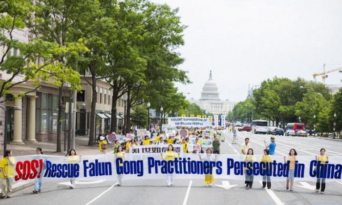 Надпись на плакате «SOS! Помогите остановить репрессии последователей Фалуньгун в Китае!». Фото: Эдвард Дай/Великая Эпоха