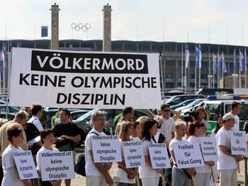 Активисты Фалуньгун стоят на олимпийском стадионе 18 августа 2007 года в Берлине перед плакатом: «Геноцид – не олимпийский вид спорта». По данным Коалиции по расследованию преследований Фалуньгун в Китае (CIPFG), практикующие Фалуньгун подвергаются пыткам и преследованию в стране, проводившей Олимпийские игры 2008. Фото с сайта Epoch Times Deutschland