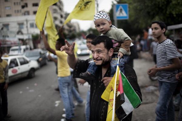 Фоторепортаж о палестинцах, празднующих подписание соглашения о примирении между ХАМАС  и ФАТХ. Фото: MOHAMMED ABED/AFP/Getty Images