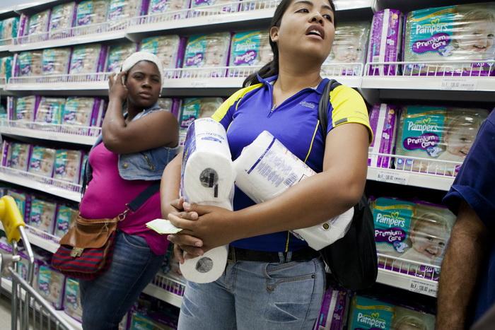 Жители Венесуэлы туалетную бумагу ищут с помощью смартфонов. Фото: LEO RAMIREZ/AFP/Getty Images