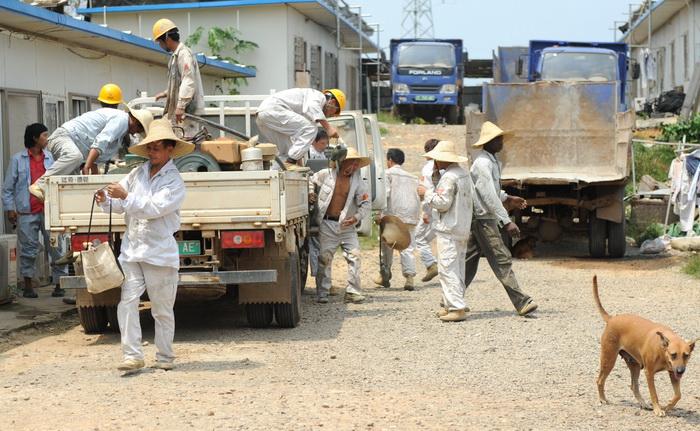 Рабочие из Китая и Буркина-Фасо, которых наняла на работу китайская государственная компании гидроэнергетики и строительства Sinohydro, возвращаются в свои общежития после рабочего дня в Бате, Экваториальная Гвинея. Фото: ABDELHAK SENNA/AFP/Getty Images