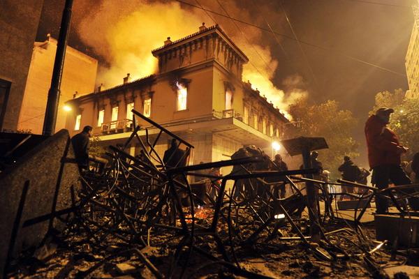В Афинах горят дома и планы правительства.  В беспорядках, прошедших в ночь на понедельник в Афинах, сгорели около 45 домов. Фото: LOUISA GOULIAMAKI/AFP/Getty Images