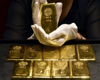 34227939949e Сотрудник магазина компании Tanaka Kikinzoku в Токио показывает слиток  золота весом в 1 кг. Цены