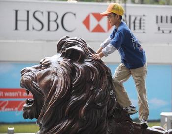 Мальчик играется на одном из двух львов, охранявших штаб-квартиру банка HSBC в Центральном районе Гонконга. Фото: MIKE CLARKE/AFP/Getty Images