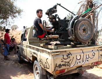 Ливийский повстанец на страже восточных ворот при входе в столицу Ливии Триполь. Повстанческий Национальный переходный совет обьявил конец «эпохи Каддафи» и вследствии продолжительных боев взял под контроль большую часть столицы страны. Фото: MAHMUD TURKIA/AFP/Getty Images