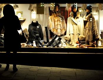 Итальянцы осматривают витрины  магазинов роскошных товаров в Кортина д'Ампеццо в Италии 15 января 2012 года. Итальянские власти под Новый год начали проводить налоговые рейды в ресторанах, барах, магазинах роскошных товаров и проверку владельцев роскошных автомобилей в эксклюзивном горнолыжном курорте Кортина д'Ампеццо из-за слишком завышенного (около 400 %) товарооборота на предприятиях курорта по сравнению с предыдущим сезоном. Проверено также 42 владельца из числа 133 роскошных автомобилей, которые заявили налоговым службам о своем доходе  менее чем 30 000 евро в год. Фото: ALBERTO PIZZOLI/AFP/Getty Images