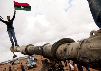 После свержения ливийского правительства в Ливии находится бесчисленное количество оружия. Тут повстанцы окружили танк армии Каддафи, разбомбленный французскими ВВС. Фото: sueddeutsche.de