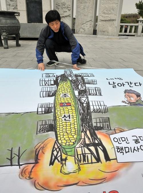 Сбежавший из Северной Кореи художник показывает карикатуру запуска ракеты Северной Кореей. Фото: JUNG YEON-JE/AFP/GettyImages